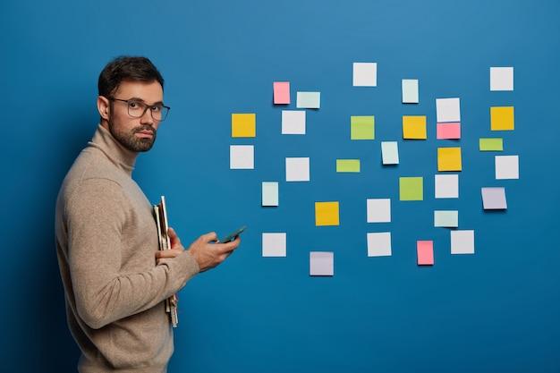Trabajador masculino confiado organiza notas coloridas en la pared azul para escribir ideas de proyectos, usa el teléfono móvil, busca información en internet