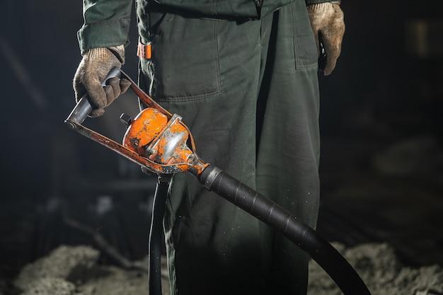 Trabajador masculino elimina el exceso de oxígeno después de verter hormigón húmedo en un molde con varillas de metal para crear pilares de hormigón armado