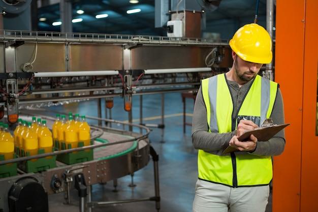 Trabajador masculino escribiendo en el portapapeles en la fábrica de jugos