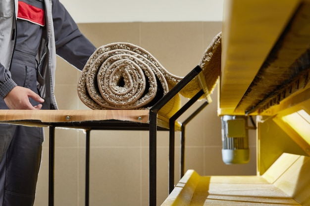 Trabajador masculino limpieza de alfombras en el equipo de lavadora automática y secadora en la lavandería