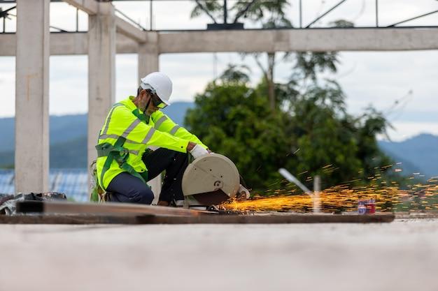 Trabajador mayor asiático cortando acero en el sitio de construcción de la armadura del techo