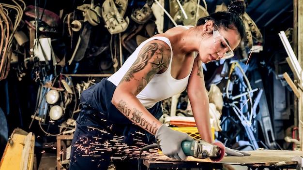 Trabajador mecánico atractivo de la mujer joven que repara un coche de época en el garaje antiguo.