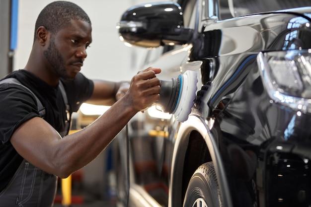 Trabajador mecánico de automóviles pulido de automóviles en el servicio de reparación de automóviles