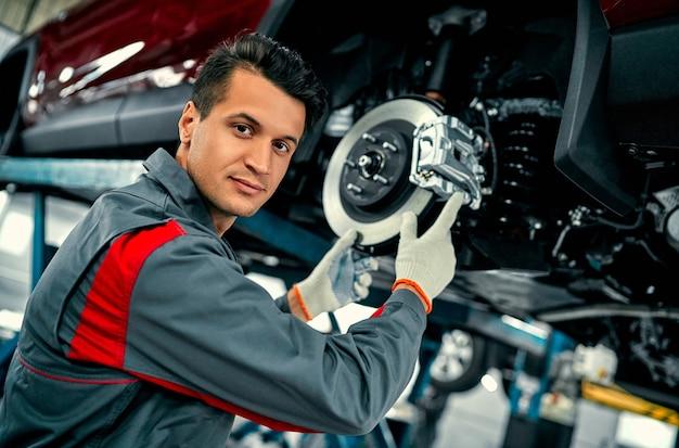 Trabajador mecánico de automóviles que repara la suspensión del automóvil levantado en la estación de taller de reparación de automóviles