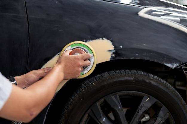 Trabajador mecánico de la mano del primer que enarena puliendo la carrocería del coche y preparándose para pintar en el servicio de la estación