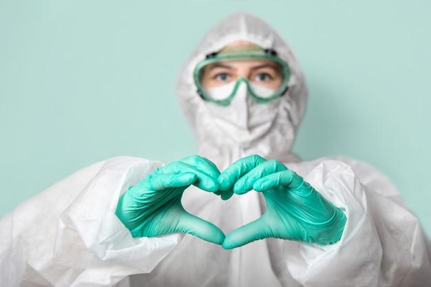 Trabajador médico en gafas de seguridad, máscara y traje hace un signo de corazón.