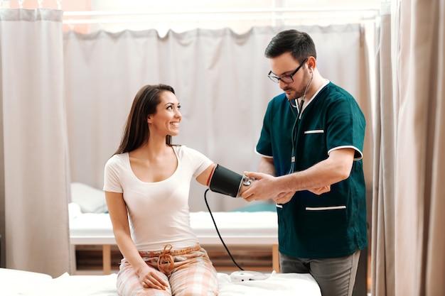 Trabajador médico de pie y medir la presión arterial.