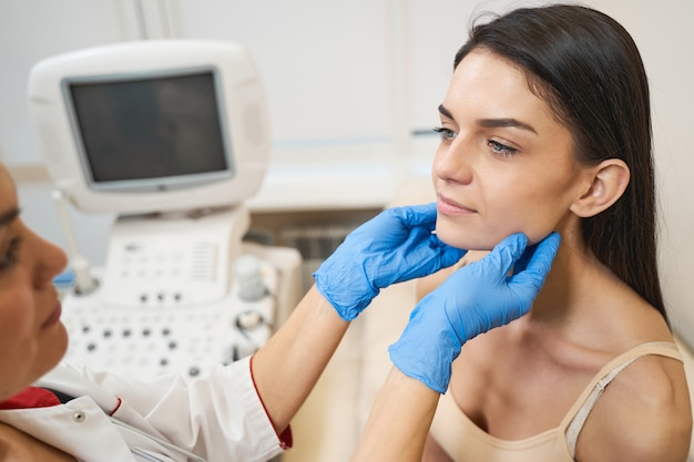 Trabajador médico profesional de pie frente a su paciente mientras realiza un chequeo de las glándulas tiroideas