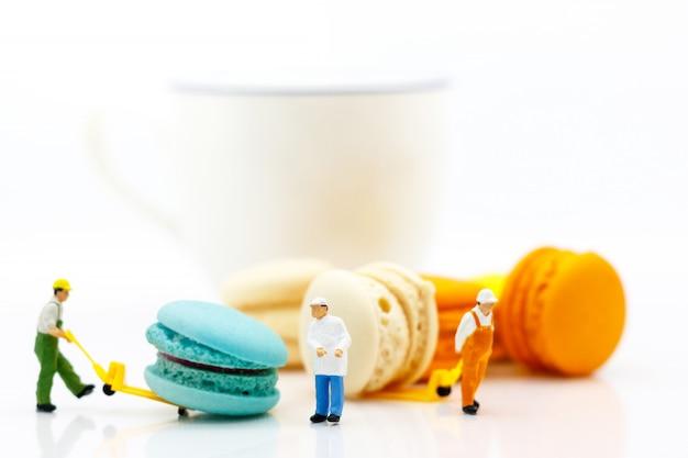 Trabajador miniatura mueve a macaron con taza de café.
