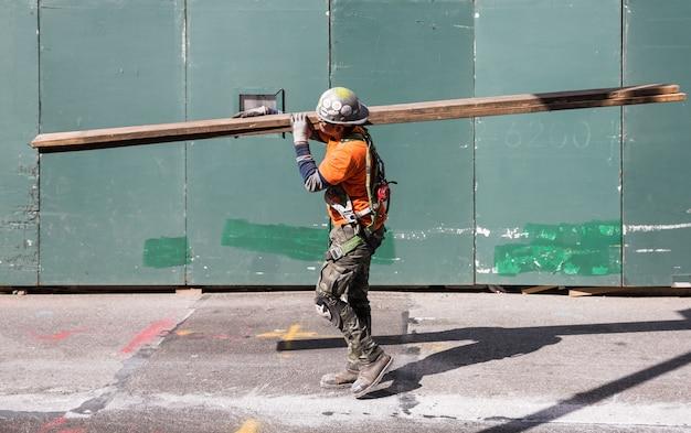 El trabajador en mono lleva tablas en el sitio de construcción