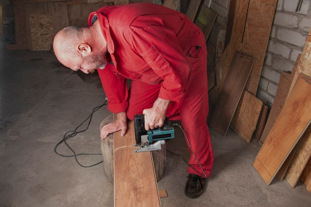 Un trabajador con un mono rojo con una herramienta eléctrica en un taller está aserrando un laminado con una sierra de calar eléctrica