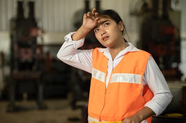 Trabajador de mujer cansada trabajo duro trabajo asiático en fábrica caliente secándose el sudor