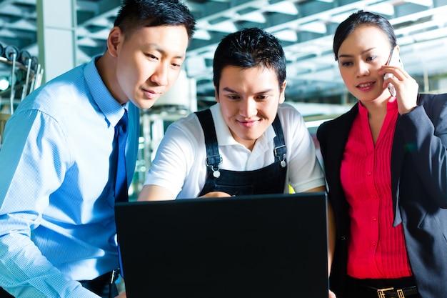Trabajador o gerente de producción y servicio al cliente, busque en una computadora portátil en una fábrica textil y ayude por teléfono