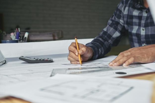 Trabajador de la oficina de arquitectura dibujando bocetos en la oficina