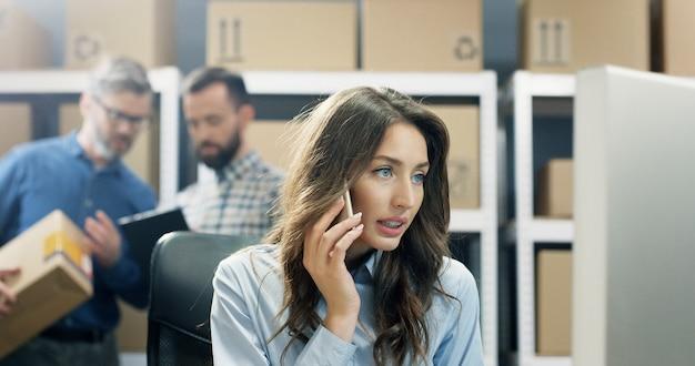 Trabajador de oficina de correos hermosa joven hablando por teléfono móvil mientras trabajaba en la computadora.