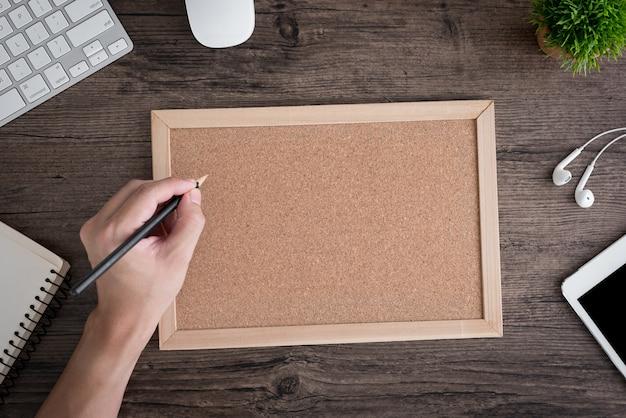 Trabajador en la oficina escribiendo en el tablero de corcho