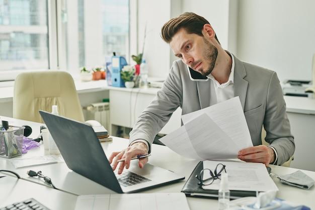 Trabajador de oficina joven ocupado en cliente de consultoría de ropa formal en el teléfono móvil mientras mira los datos en la pantalla del portátil y lee documentos financieros