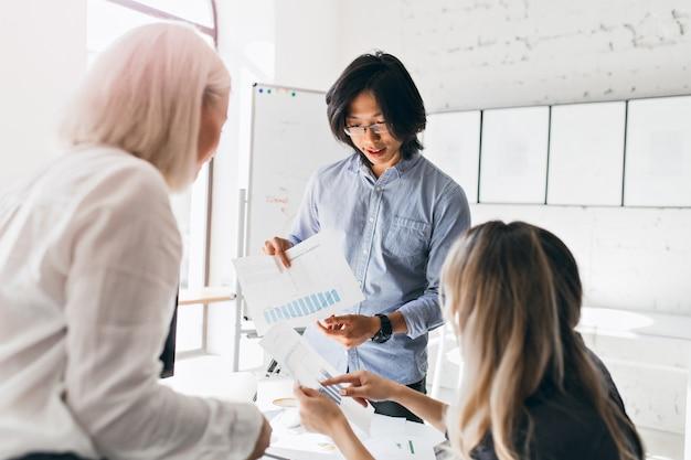 Trabajador de oficina masculino asiático con reloj de pulsera sosteniendo documentos con diagramas mientras habla con colegas femeninas