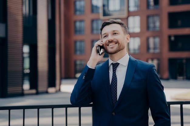 Trabajador de oficina masculino feliz en traje azul hablando por teléfono con un colega o socio sobre el próximo proyecto comercial, planificando las cosas, disfrutando de la llamada mientras está de pie solo con edificios de oficinas detrás de él