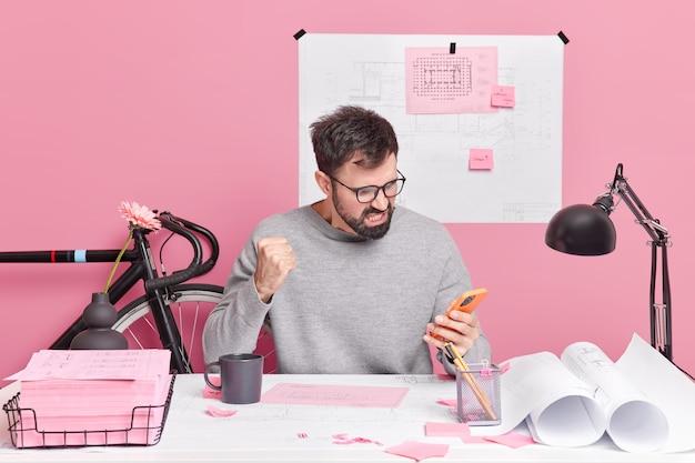 Trabajador de oficina masculino indignado enojado mira molesto al teléfono inteligente aprieta el puño distraído de las poses de trabajo en el espacio de coworking