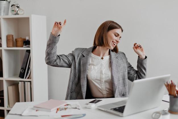 Trabajador de oficina positivo en camisa blanca bailando mientras está sentado en la mesa de estantes con documentos.