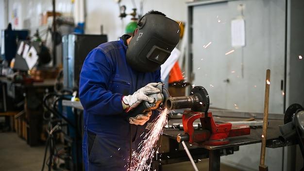 Trabajador operando una amoladora angular y haciendo muchas chispas