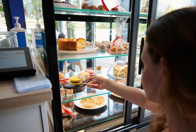 Trabajador de pastelería seleccionando un delicioso macarrón amarillo de una vitrina llena de pasteles y deliciosos dulces. escaparate en una cafetería con una gran variedad de pasteles.