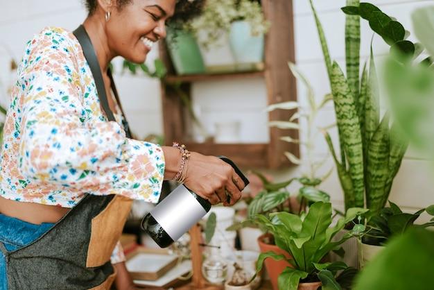 Trabajador de pequeñas empresas nebulizando plantas con un rociador de agua