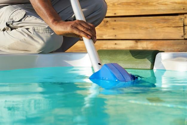 Trabajador del personal del hotel africano limpiando la piscina
