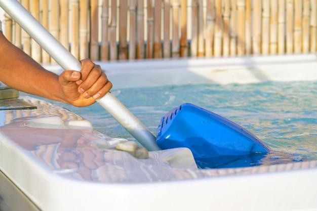 Trabajador del personal del hotel limpiando la piscina