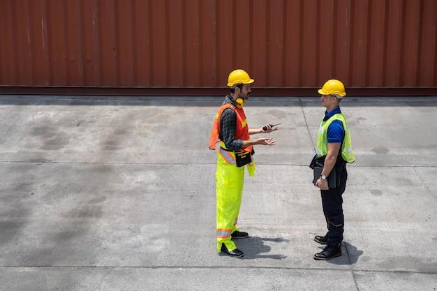 Trabajador del personal de pie y comprobando la caja de contenedores del buque de carga para exportación e importación