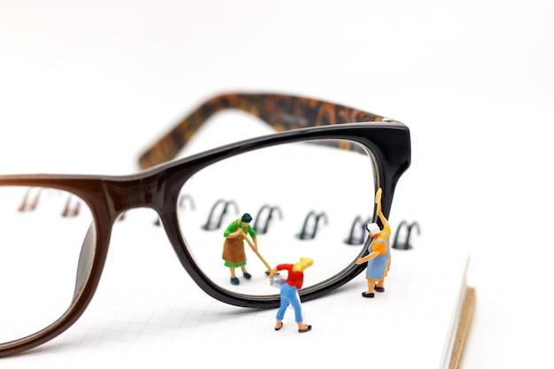 Trabajador de personas miniatura limpieza de gafas en el libro. concepto de visión clara.