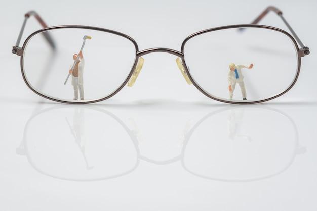 Trabajador de personas en miniatura limpieza ojos gafas