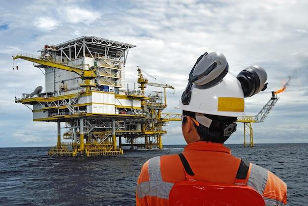 Trabajador petrolero y plataforma petrolera