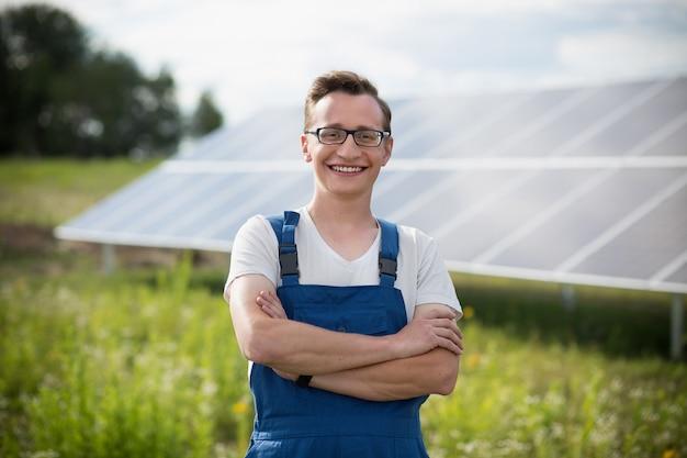Trabajador de pie en el campo con energía solar con paneles solares en el backstage.