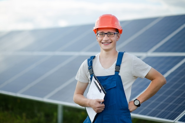 Trabajador en pie de casco, paneles solares detrás de él.