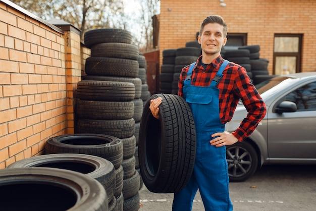 Trabajador en la pila de neumáticos, servicio de neumáticos
