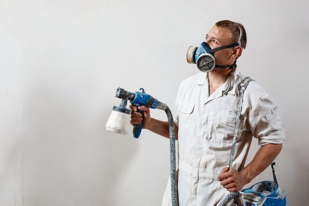 Trabajador pintando la pared con pistola en color blanco.
