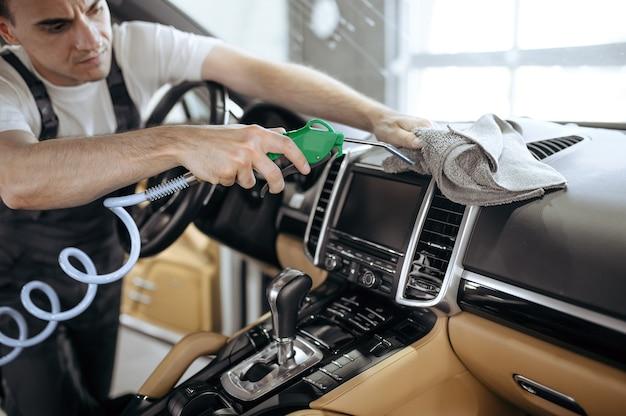 Trabajador con pistola de aire limpia la rejilla del conducto de aire del coche, la limpieza en seco y los detalles.