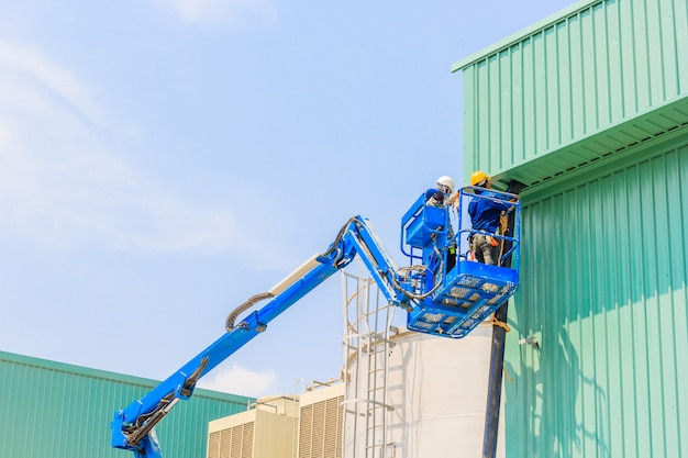 Trabajador en una plataforma elevadora de tijera hidráulica plataforma hacia el techo de una fábrica