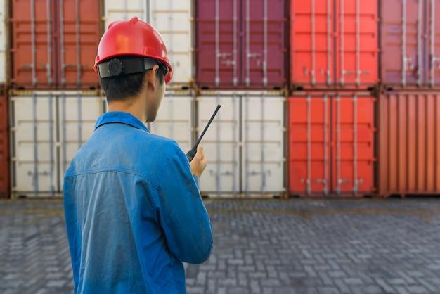 Trabajador portuario que habla en el walkie-talkie para controlar el contenedor de carga en un puerto industrial