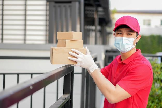 El trabajador postal pone la caja y se para frente a la casa para dar orden al cliente