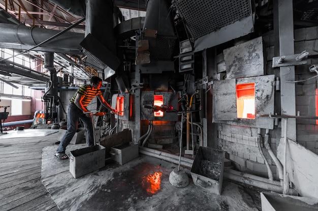 Trabajador de producción de vidrio que trabaja con equipos de la industria en el fondo de la fábrica