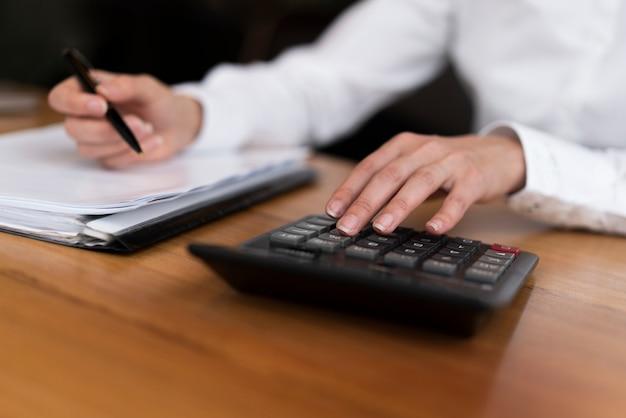 Trabajador profesional irreconocible escribiendo en calculadora