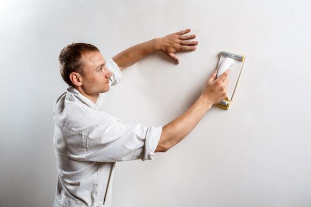 Trabajador pulido pared blanca con papel de lija