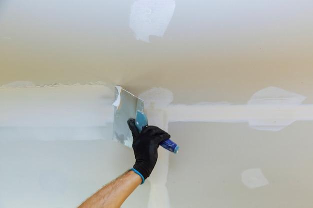 Trabajador puttied pared con una espátula de pintura