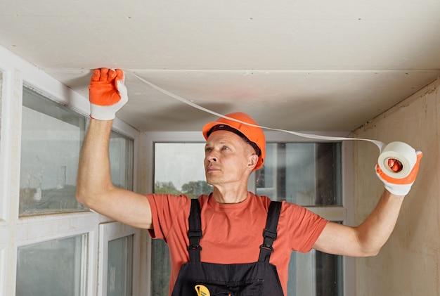 El trabajador que fija la malla a las uniones entre las placas de yeso