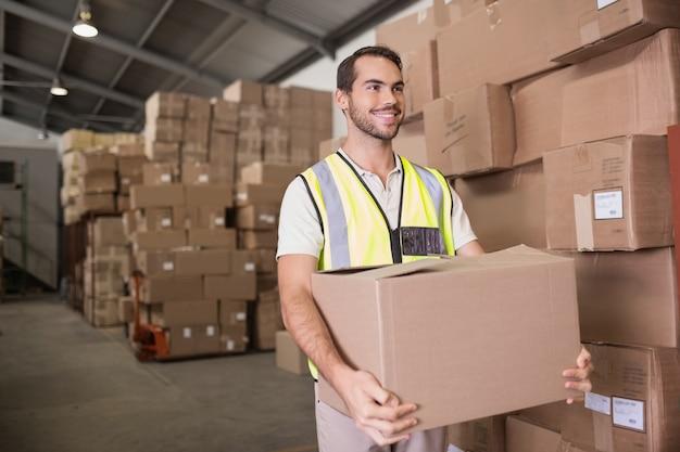 Trabajador que lleva la caja en el almacén