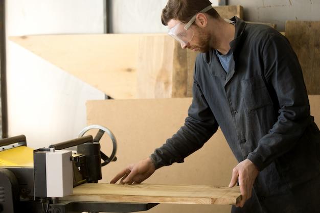 Trabajador que produce madera en el aserradero local