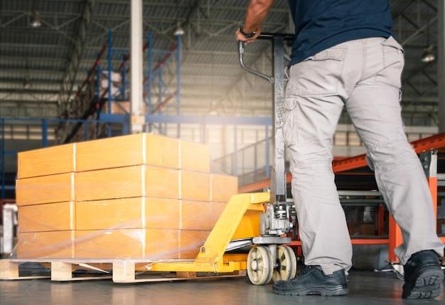 Trabajador que trabaja con transpaleta manual descargando cajas de carga en el almacén.